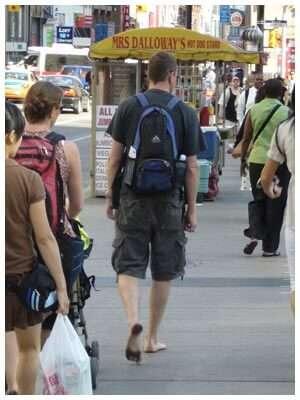 Man barefoot on city street