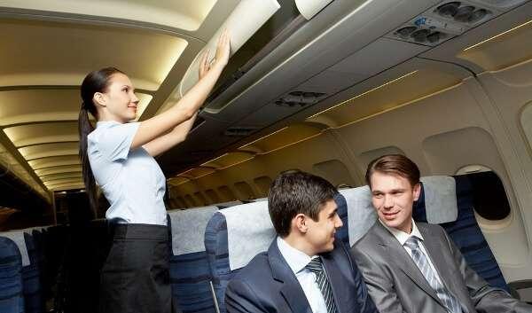 Flight Attendant Closing Overhead Bin