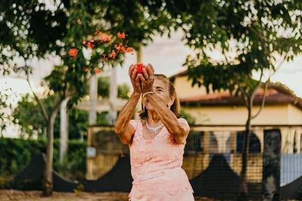 Senior Lady Throwing Flowers